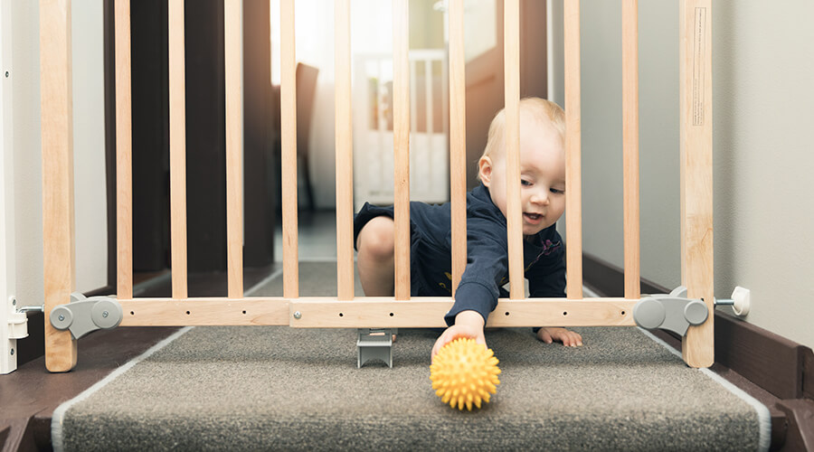 baby playing with ball at stair gate